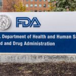 The image contains a stone sign reading: FDA, U.S. Department of Health and Human Services Food and Drug Administration. There is a corporate building in the background and soil ground in front of the sign.